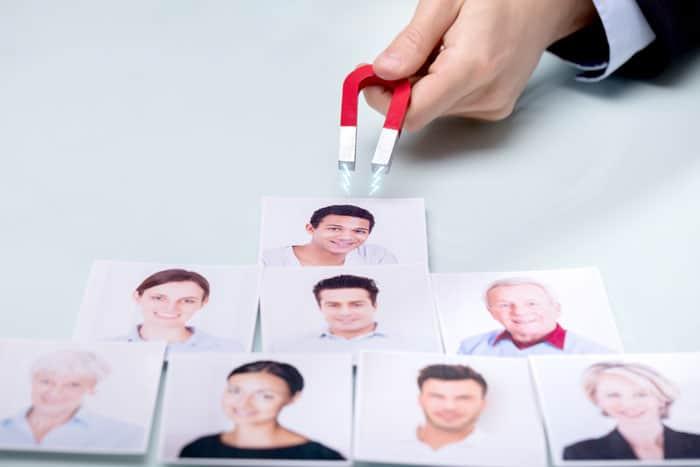 Fotos de pessoas sendo atraídas por um íman, para exemplificar como o marketing atrai um lead. que posteriormente acabará no pré-vendas e para a empresa vender mais.