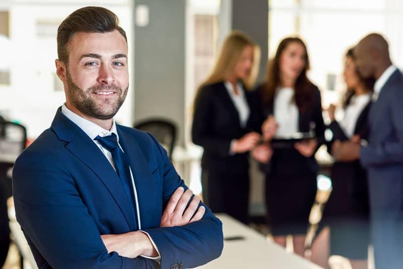 Vendedor em foco, enquanto outros discutem modelos de vendas.